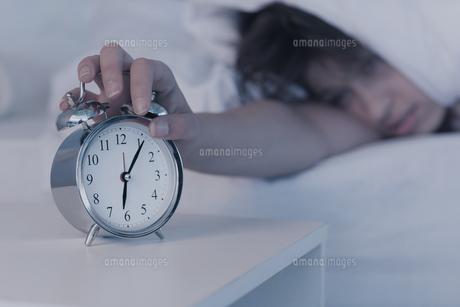 Beautiful brunette hitting alarm clock from under duvetの写真素材 [FYI00002956]