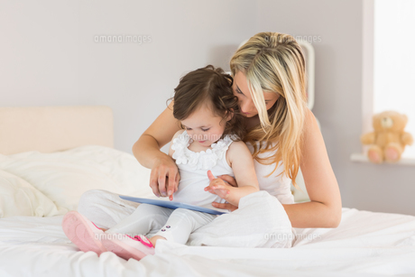 Mother and daughter using digital tablet on bedの写真素材 [FYI00002959]