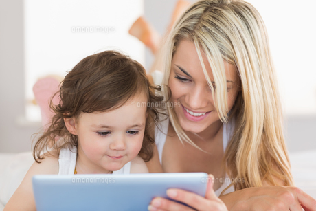 Mother and daughter using digital tablet on bedの写真素材 [FYI00002963]