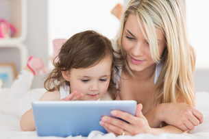 Mother and young daughter digital tablet on bedの写真素材 [FYI00002964]