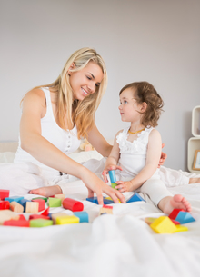 Mother and daughter playing with building blocks on bedの写真素材 [FYI00002966]