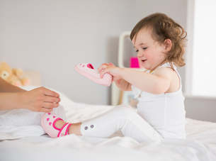 Mother dressing up young daughter on bedの写真素材 [FYI00002968]