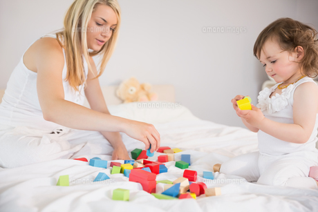 Mother and daughter playing with building blocks on bedの写真素材 [FYI00002969]