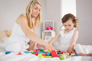 Mother and daughter playing with building blocks on bedの写真素材 [FYI00002970]