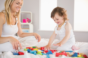 Mother and daughter playing with building blocks on bedの写真素材 [FYI00002972]