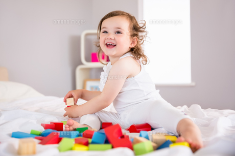 Cute girl playing with building blocks on bedの写真素材 [FYI00002973]
