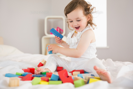 Cute girl playing with building blocks on bedの写真素材 [FYI00002974]