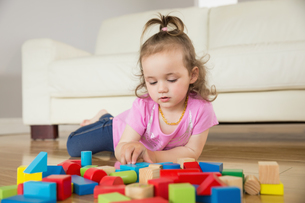 Girl playing with building blocks on floorの写真素材 [FYI00002976]
