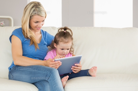 Mother and daughter using digital tablet on couchの写真素材 [FYI00002977]