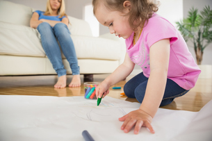 Girl drawing in the living room with mother sitting behindの写真素材 [FYI00002978]