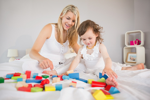 Mother and daughter playing with building blocks on bedの写真素材 [FYI00002980]