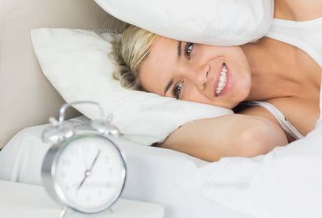 Woman an covering ears with pillow as she looks at alarm clockの写真素材 [FYI00002995]