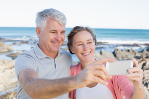 Happy casual couple taking a selfie by the coastの写真素材 [FYI00003002]
