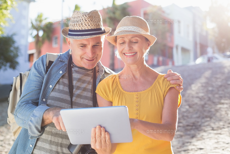 Happy tourist couple using tablet pc in the cityの写真素材 [FYI00003020]