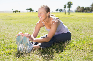 Fit mature woman warming up on the grassの写真素材 [FYI00003029]
