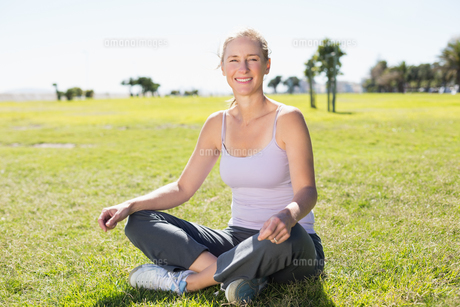 Fit mature woman sitting in lotus pose on the grassの素材 [FYI00003032]
