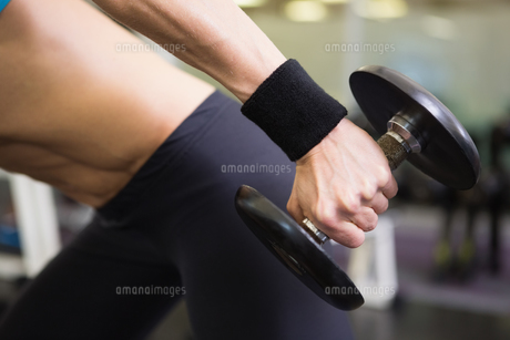 Mid section of fit woman exercising with dumbbell in gymの写真素材 [FYI00003038]