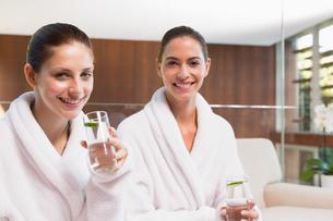 Smiling women in bathrobes drinking waterの写真素材 [FYI00003045]