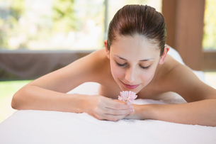 Beautiful woman holding flower on massage table at spa centerの写真素材 [FYI00003064]