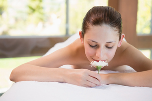 Beautiful woman holding flower on massage table at spa centerの素材 [FYI00003068]
