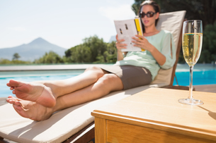 Woman reading book by pool with champagne in foregroundの写真素材 [FYI00003080]