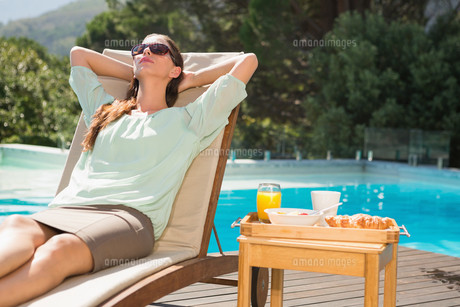 Woman relaxing by pool with breakfast on tableの写真素材 [FYI00003084]