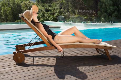 Beautiful woman in bikini relaxing by swimming poolの写真素材 [FYI00003088]