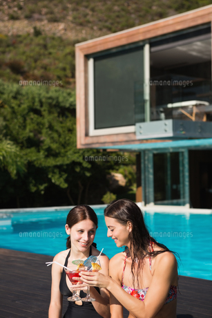 Women holding drinks by swimming poolの写真素材 [FYI00003089]
