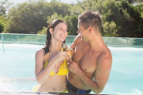 Couple with champagne flutes by swimming poolの写真素材 [FYI00003090]