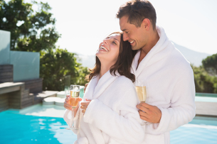 Cheerful couple with champagne flutes by swimming poolの写真素材 [FYI00003092]