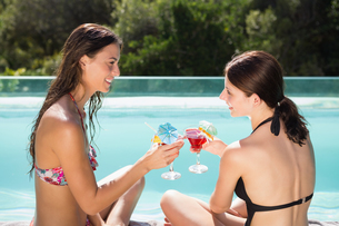 Women toasting drinks by swimming poolの写真素材 [FYI00003093]