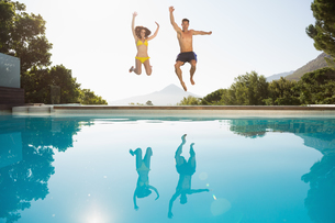 Cheerful couple jumping into swimming poolの写真素材 [FYI00003096]