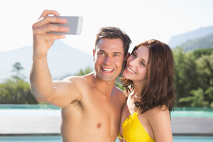 Couple taking picture of themselves by swimming poolの写真素材 [FYI00003097]