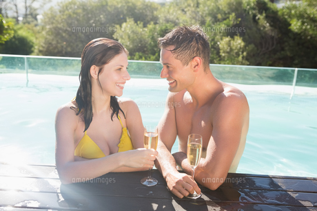 Couple with champagne flutes by swimming poolの写真素材 [FYI00003099]