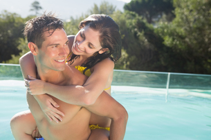 Man carrying cheerful woman by swimming poolの写真素材 [FYI00003103]