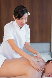 Female masseur massaging mans back at spa centerの素材 [FYI00003107]