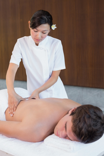 Female masseur massaging mans back at spa centerの素材 [FYI00003111]