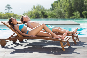 Couple resting on sun loungers by swimming poolの写真素材 [FYI00003116]