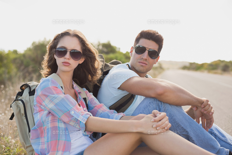 Hiking couple sitting on countryside roadの写真素材 [FYI00003129]