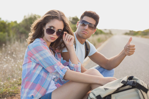 Couple hitchhiking on countryside roadの写真素材 [FYI00003131]