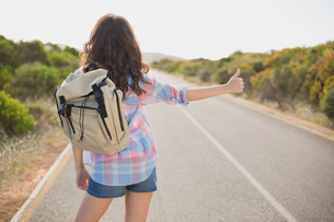 Woman hitchhiking on countryside roadの写真素材 [FYI00003132]