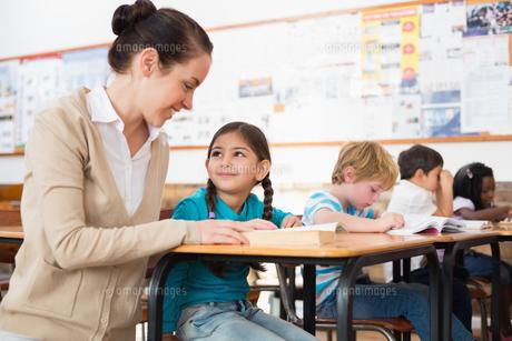 Pretty teacher helping pupil in classroomの写真素材 [FYI00003136]