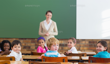 Cute pupils and teacher smiling at camera in classroomの写真素材 [FYI00003140]