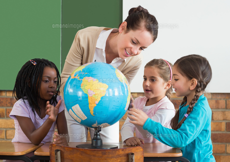 Cute pupils and teacher in classroom with globeの写真素材 [FYI00003143]