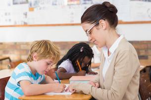 Pretty teacher helping pupil in classroomの写真素材 [FYI00003150]
