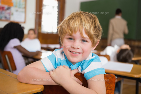 Smiling pupil sitting at his deskの写真素材 [FYI00003151]