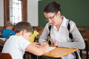 Pretty teacher helping pupil in classroomの写真素材 [FYI00003162]