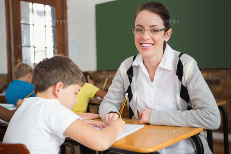 Pretty teacher helping pupil in classroom smiling at cameraの写真素材 [FYI00003164]