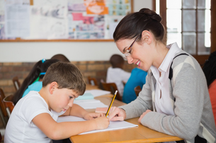 Pretty teacher helping pupil in classroomの写真素材 [FYI00003167]