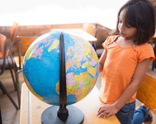 Cute little pupil looking at globe in classroomの写真素材 [FYI00003169]